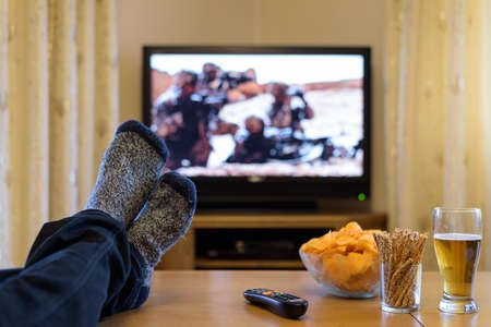 TV, television watching (war movie) with feet on table eating snacks and drinking beer Archivio Fotografico