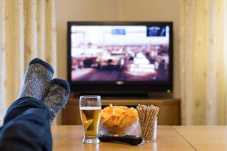 テーブルに足で戦争映画 (タンク、イラク) テレビを見て、軽食を食べて、ビールを飲んで