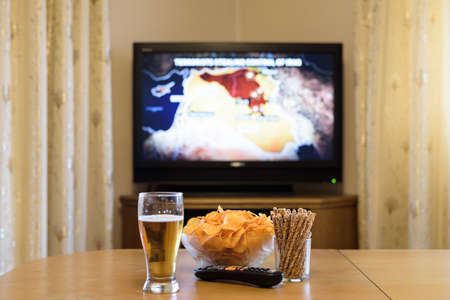 near beer: TV, television watching (map of syria, iraq, isis, news) with snacks on table