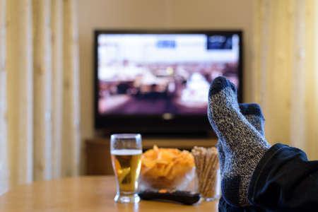 piernas hombre: viendo la película de televisión de guerra (tanques, iraq) con los pies sobre la mesa, comiendo bocadillos y bebiendo cerveza