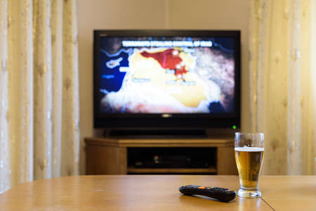 near beer: TV, television watching (map of near east) with feet on the table - stock photo