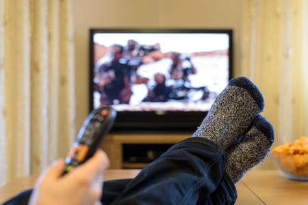 テレビ、テレビのテーブルの食事に足で (戦争映画) を見てスナックします。