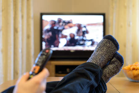 TV, television watching (war movie) with feet on table eating snacks Stock Photo