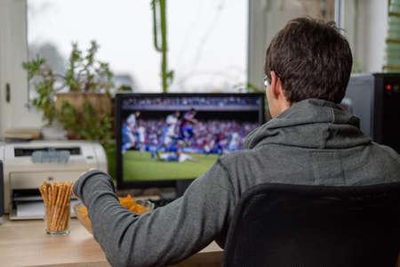 スナック テーブル - ストック フォトの上に横たわるとコンピューターの男性ゲーマー演奏サッカー ゲーム