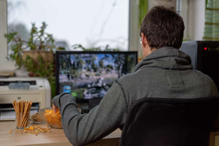 male gamer playing shooting game on computer with snacks lying on table - stock photo