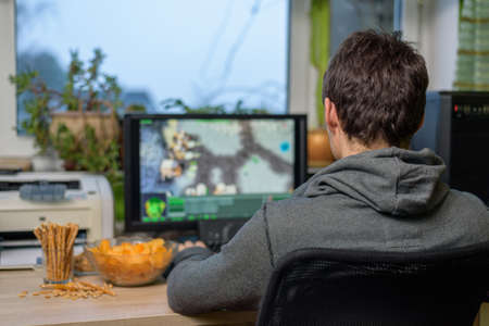 スナック テーブル - ストック フォトの上に横たわるとコンピューターの男性ゲーマー再生戦略ゲーム