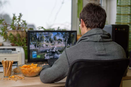 unhealthy living: male gamer playing shooting game on computer with snacks lying on table - stock photo