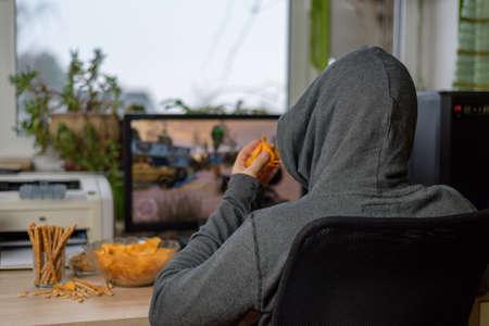 スナック テーブル - ストック フォトの上に横たわるとコンピューターの男性ゲーマー演奏シューティング ゲーム 写真素材