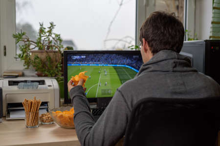 male gamer playing football game on computer with snacks lying on table - stock photo