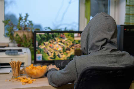 gamer: male gamer playing strategy game on computer with snacks lying on table - stock photo