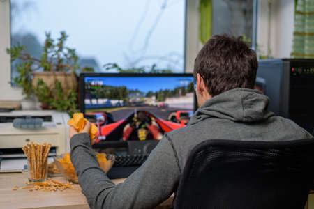 male gamer playing racing game on computer with snacks lying on table - stock photo