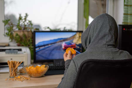 gamer: male gamer playing racing game on computer with snacks lying on table - stock photo