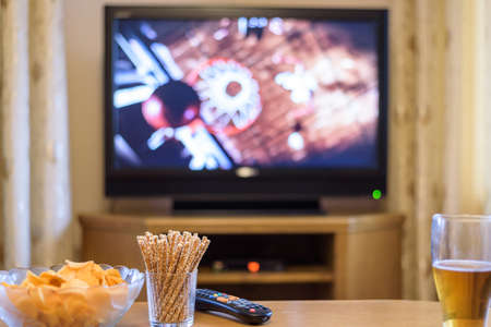 Television, TV watching (basketball game) with snacks and alcohol lying on table - stock photo