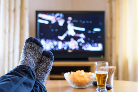 rest room: Television, TV watching (basketball game) with feet on table eating snacks and drinking beer - stock photo