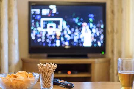 テレビ、テレビ観戦 (バスケット ボール) 軽食とアルコール表 - ストック フォトの上に横たわる