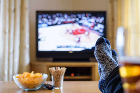 court room: Television, TV watching (basketball game) with feet on table eating snacks and drinking beer - stock photo