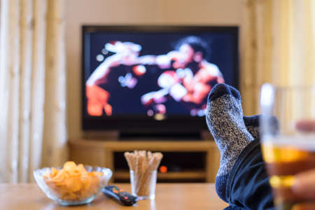 Television, TV watching (boxing match) with feet on table eating snacks and drinking beer - stock photo