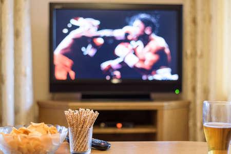 Televisión, ver la televisión (combate de boxeo) con aperitivos y alcohol extiende sobre la mesa - la foto