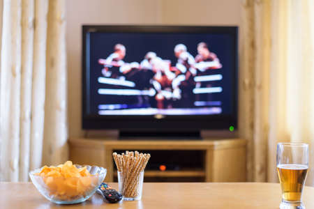 boxing match: Television, TV watching (boxing match) with snacks and alcohol lying on table - stock photo