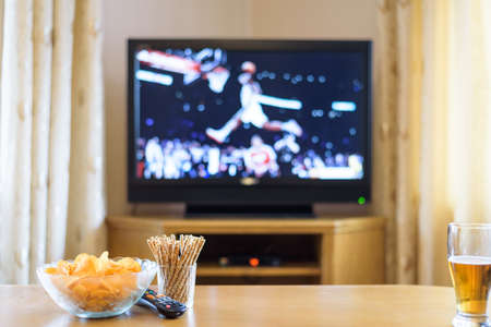 rest room: Television, TV watching (basketball game) with snacks and alcohol lying on table - stock photo