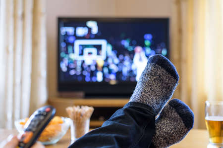 Television, TV watching (basketball game) with feet on table eating snacks and drinking beer - stock photo