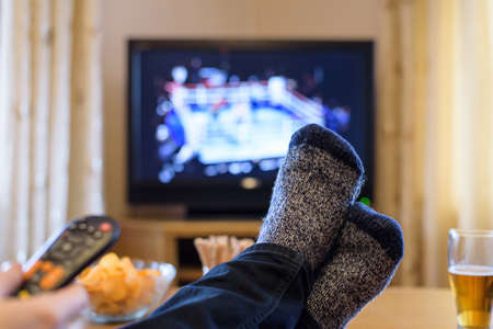 boxing match: Television, TV watching (boxing match) with feet on table eating snacks and drinking beer - stock photo