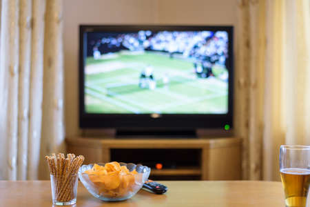 court room: Television, TV watching (tennis match) with snacks and alcohol lying on table - stock photo