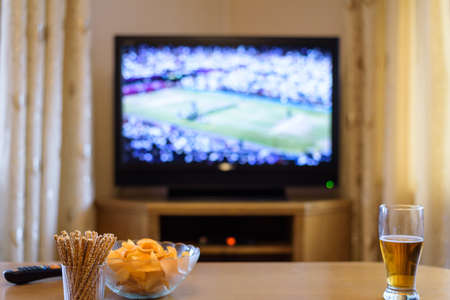 rest room: Television, TV watching (tennis match) with snacks and alcohol lying on table - stock photo
