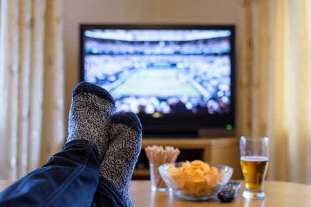 Regarder un match de tennis sur le plateau TV (télévision) avec les pieds sur la table et de manger des collations - photo