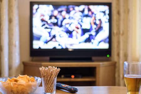 テレビ、テレビ見て (アメリカン フットボール) テレビでの試合では軽食やアルコール - ストック フォト 写真素材