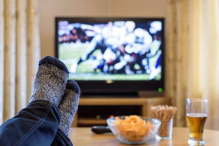 pies masculinos: el hombre mirando el partido de fútbol americano en la televisión (televisión) con los pies sobre la mesa, comiendo bocadillos de la foto -