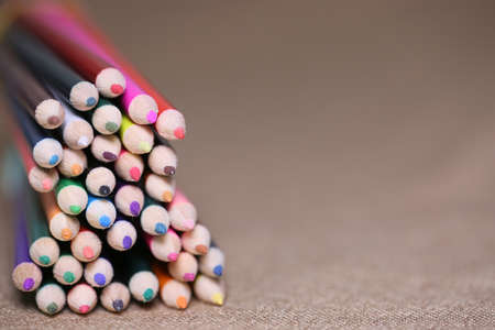Multicolored pencils on the table. A stack of colored pencils tied together. A scattering of writing supplies and stationery. Stock Photo
