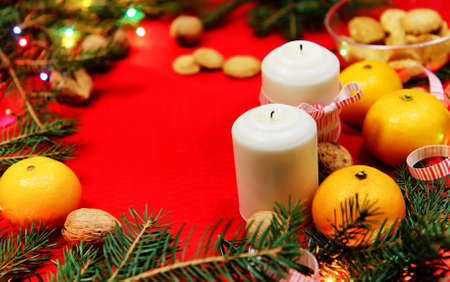 Christmas tree toys on a red napkin. Mandarins and candles on th