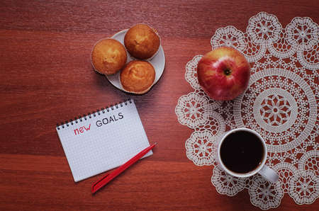 Notepad for entries on the table. Handle and paper on a wooden surface for notes. An apple and a cup with coffee with writing utensils.