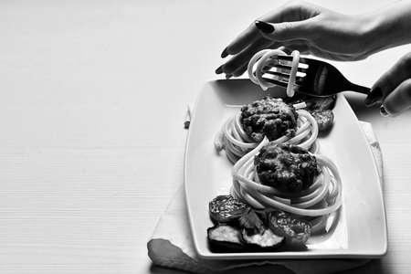 Dinner in the restaurant. Hands plates of food. Fork for eating. Stockfoto