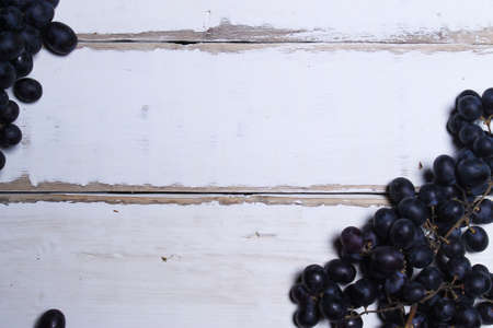 Black grapes lying on a wooden table Standard-Bild