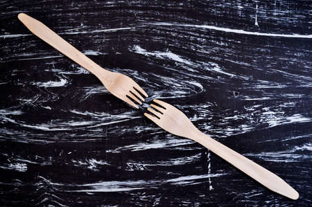 Silver fork lying on a wooden table. Cutlery for eating. Device Imagens - 98134062