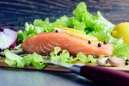 A piece of fish with vegetables on the table. Healthy food for l Standard-Bild
