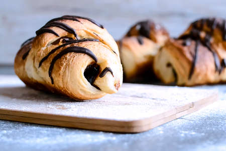 Fresh croissants with chocolate on the table. Delicious Breakfas