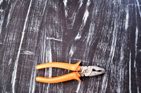 Pliers for repair work lying on the table. Repair tools in the h
