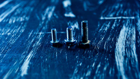 Nuts for repairs lying on a wooden table. Iron nuts and screws f