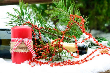 Champagne and Christmas decorations in the snow. Holiday decorat