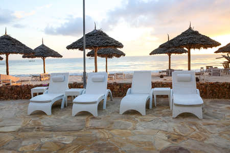 Beach with sun loungers and a place for rest at sunset. A beauti Imagens