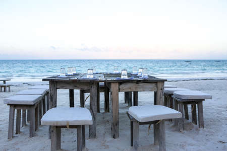 Wooden table and chairs on the beach. Furniture for lounging on Imagens