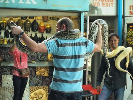 RATCHABURI,THAILAND-February 25 : Tourist Take Photo With Snake Damneonsaduak Floating Market on February 25,2014 in Ratchaburi,Thailand.
