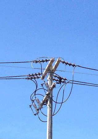 Electricity pylons, poles on blue cloudy sky Stock Photo