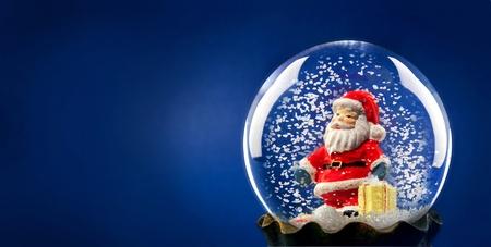 Santa Claus avec de la neige dans une sphère Banque d'images - 9834927
