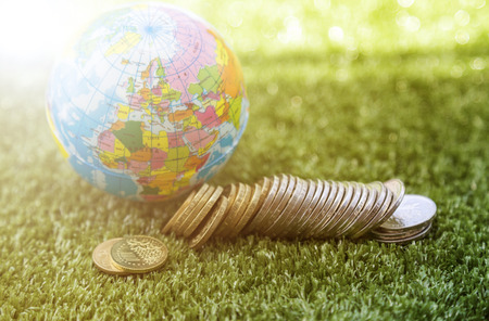 small world: Small world and coins money on the grass surface Stock Photo