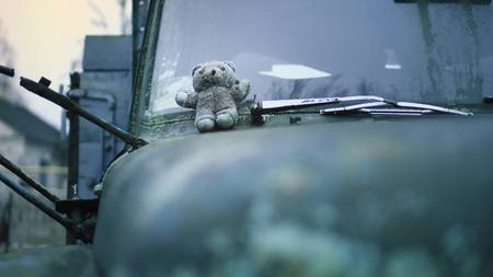 Old abandoned military truck and childrens toy. War. Close up view toy and hood of car