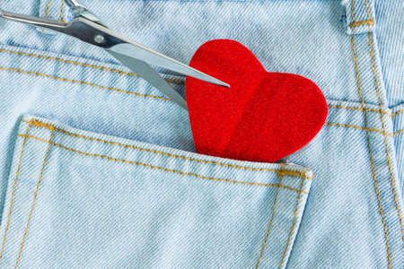 scissors cut heart love on jeans background photo